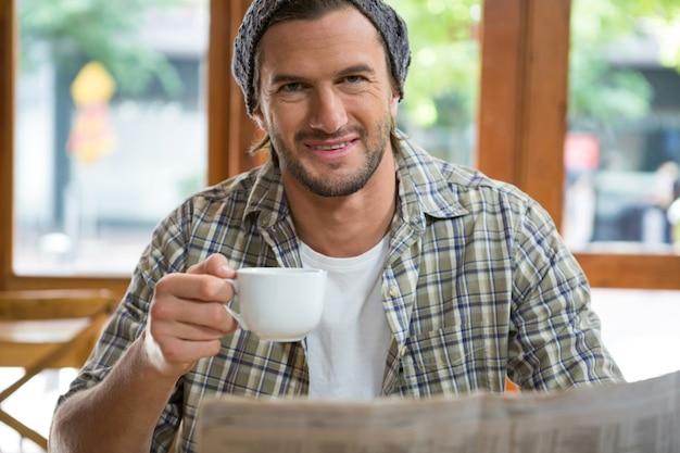 Portrait de jeune homme souriant tenant une tasse de café au café