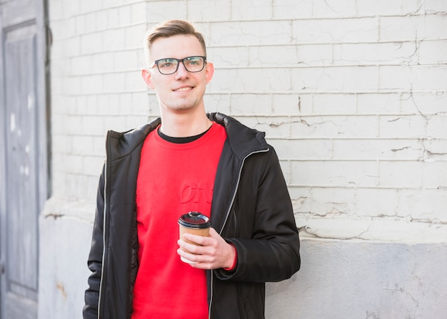 Portrait d'un jeune homme souriant tenant une tasse de café à emporter à la recherche de suite