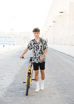 Portrait d'un jeune homme souriant à vélo