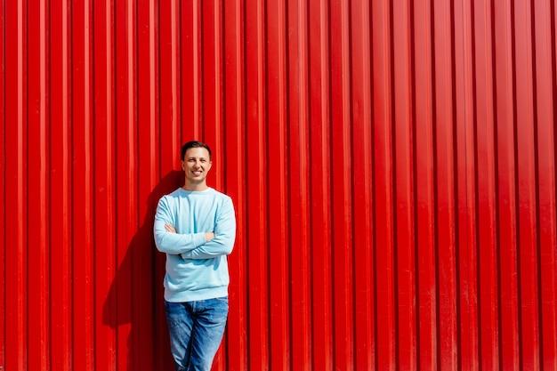 Portrait de jeune homme souriant en veste bleue sur le fond du mur rouge