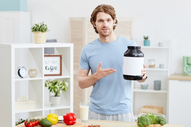 Portrait de jeune homme sportif pointant sur bouteille avec nutrition sportive et debout dans la cuisine