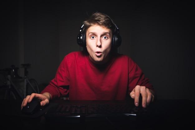 Portrait d'un jeune homme surpris à l'aide d'un ordinateur la nuit