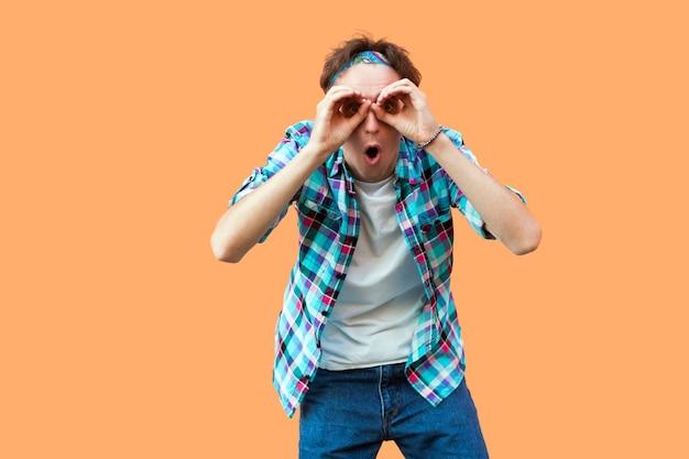 Portrait d'un jeune homme surpris en chemise à carreaux bleu décontractée et bandeau debout avec des jumelles mains geste sur les yeux, regardant avec un visage choqué. tourné en studio intérieur, isolé sur fond orange