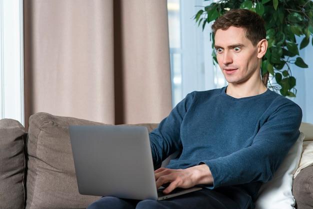 Portrait d'un jeune homme surpris et choqué utilisant un ordinateur portable en tapant sur un ordinateur avec un visage excité