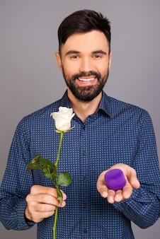 Portrait de jeune homme tenant la boîte avec bague de mariage et rose blanche