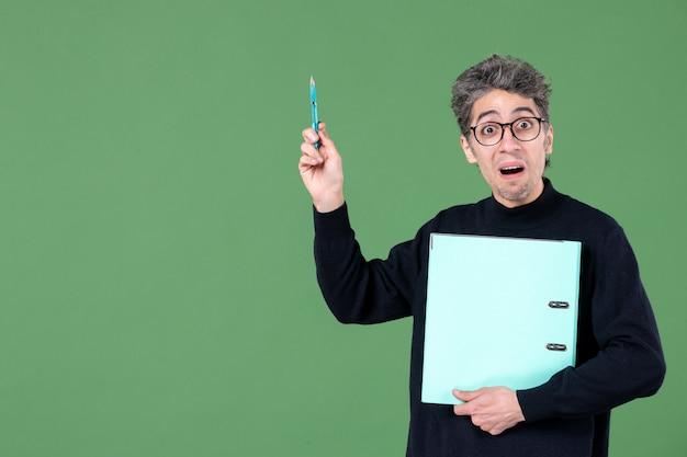 Portrait de jeune homme tenant des documents tourné en studio sur fond vert travail de leçon d'affaires enseignant