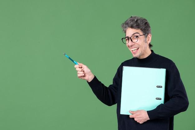 Portrait de jeune homme tenant des documents tourné en studio sur fond vert travail de professeur d'entreprise