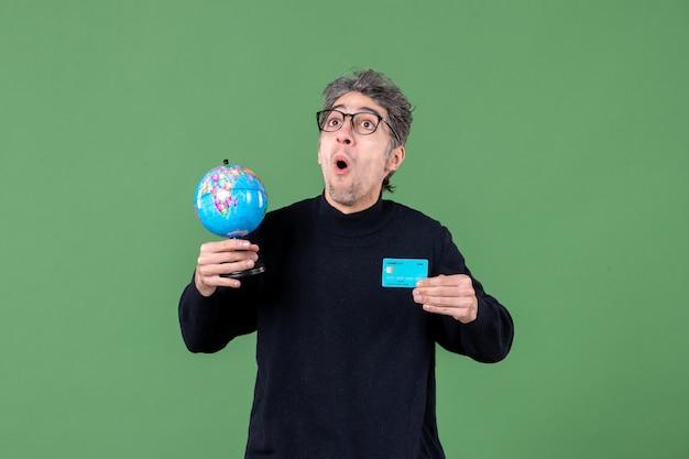 Portrait de jeune homme tenant un globe terrestre et une carte de crédit fond vert argent professeur banque nature