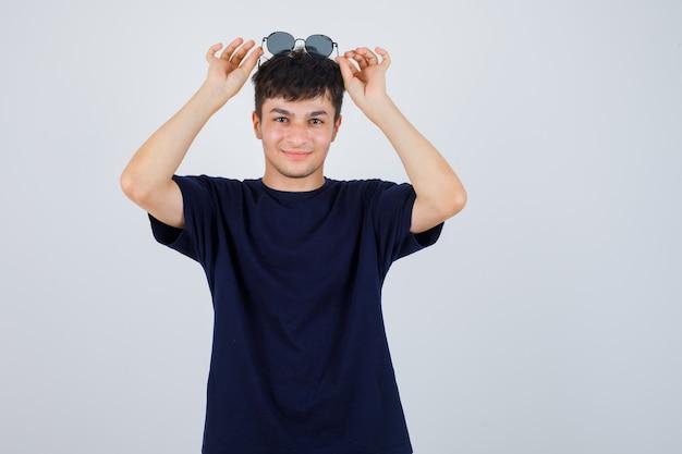 Portrait de jeune homme tenant des lunettes de soleil sur la tête en t-shirt noir et à la joyeuse vue de face
