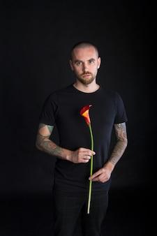 Portrait de jeune homme tenant une seule fleur de calla rouge sur fond noir, carte de voeux ou concept