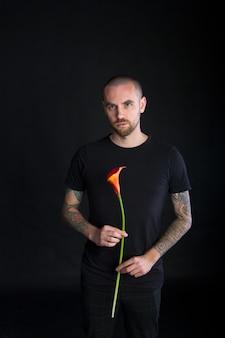 Portrait de jeune homme tenant une seule fleur de calla rouge isolé