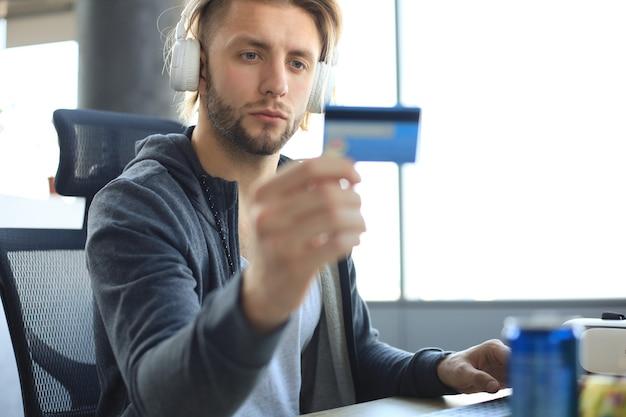 Portrait d'un jeune homme tenant et utilisant une carte de crédit pour recharger l'argent du jeu.