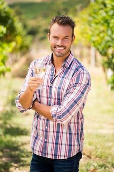 Portrait de jeune homme tenant un verre à vin