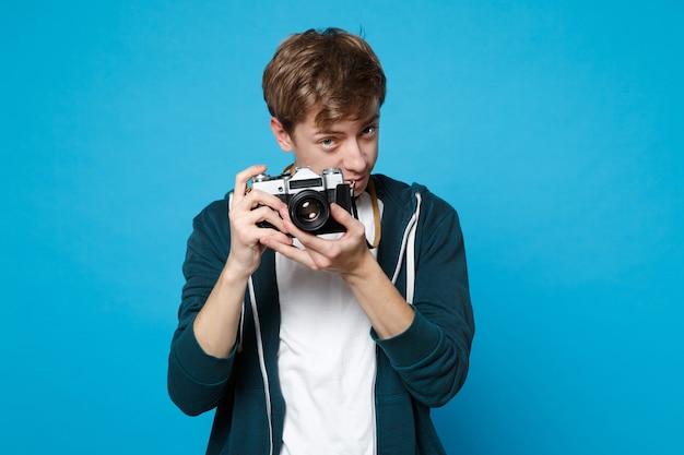 Portrait de jeune homme en tenue décontractée tenant des photos sur un appareil photo vintage rétro isolé sur un mur bleu. concept de mode de vie des émotions sincères des gens.