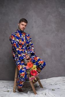Portrait, jeune, homme, tenue, fleur, mains, regarder appareil-photo