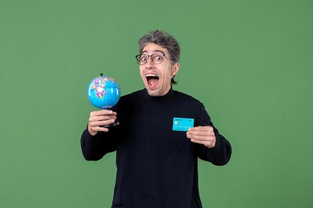 Portrait, de, jeune homme, tenue, globe terre, et, carte crédit, fond vert, mâle, enseignant, banque, nature