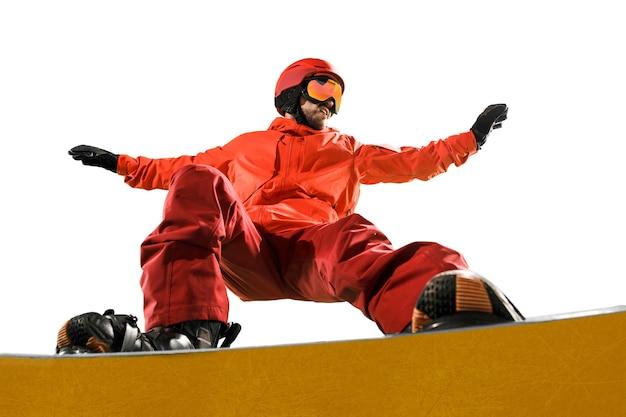 Portrait de jeune homme en tenue de sport avec snowboard isolé sur fond de studio blanc. l'hiver, le sport, le snowboard, le snowboarder, l'activité, le concept extrême