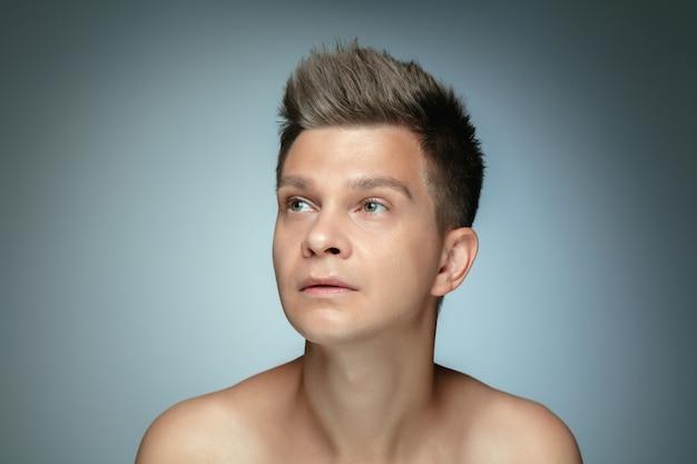 Portrait de jeune homme torse nu isolé sur mur gris