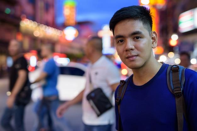 Portrait de jeune homme touriste asiatique beau explorer à chinatown à bangkok, thaïlande