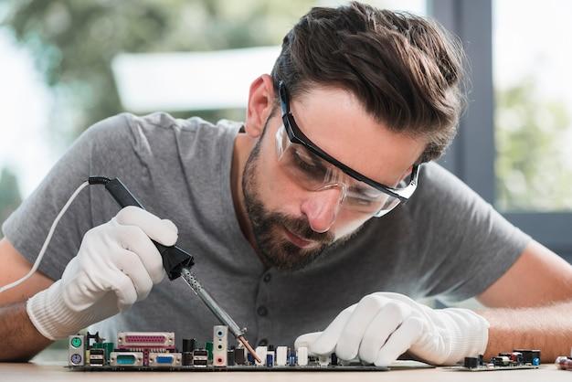Portrait d'un jeune homme en train de souder un circuit informatique en atelier