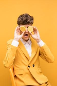 Portrait de jeune homme avec des tranches de citron devant les yeux dans une scène jaune