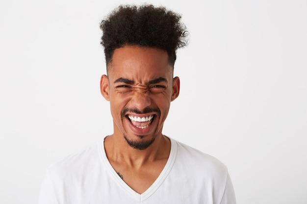 Portrait de jeune homme triste bouleversé aux cheveux bouclés porte t-shirt semble déprimé et lèvres courbes isolé sur mur blanc