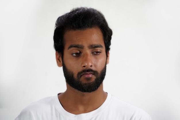 Un portrait de jeune homme triste isolé sur blanc