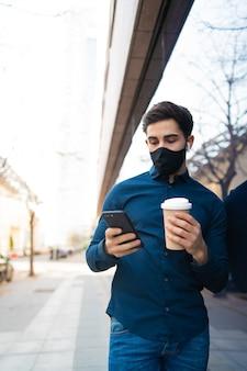 Portrait de jeune homme utilisant son téléphone portable et tenant une tasse de café tout en se tenant à l'extérieur dans la rue. nouveau concept de mode de vie normal. concept urbain.
