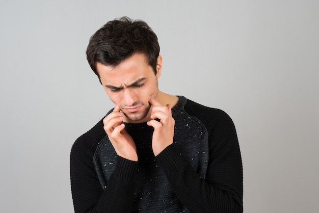 Portrait de jeune homme en vêtements décontractés regardant l'inconvénient sur un mur gris