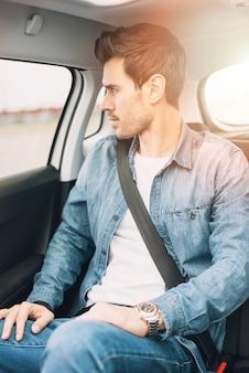 Portrait d'un jeune homme voyageant dans la voiture