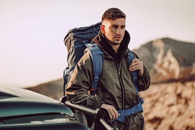 Portrait D'un Jeune Homme Voyageur Dans L'équipement De Randonnée Debout Près De Sa Voiture Tout-terrain Photo Premium