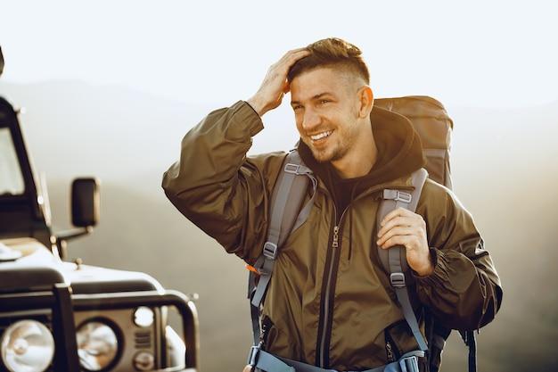 Portrait d'un jeune homme voyageur dans l'équipement de randonnée debout près de sa voiture tout-terrain