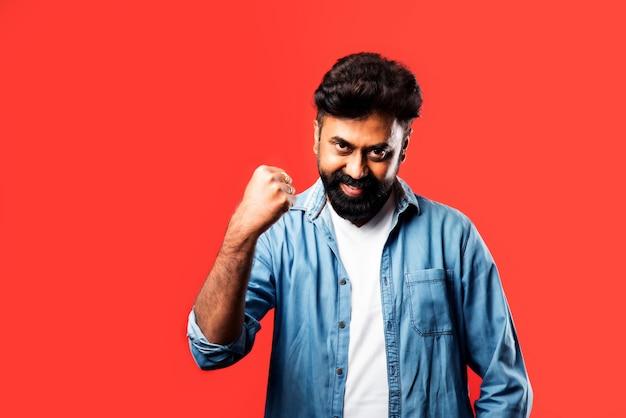 Portrait d'un jeune indien satisfait célébrant le succès sur le rouge