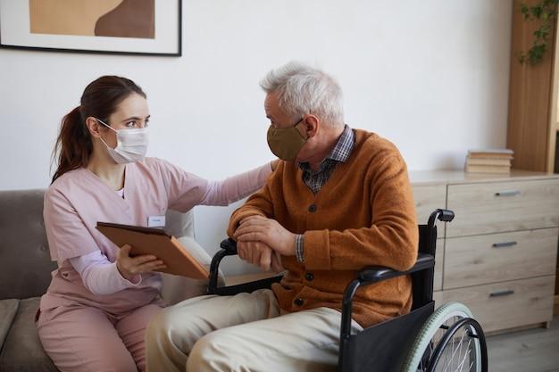 Portrait d'une jeune infirmière aidant un homme âgé en fauteuil roulant à l'aide d'une tablette numérique à la maison de retraite, tous deux portant des masques, espace pour copie