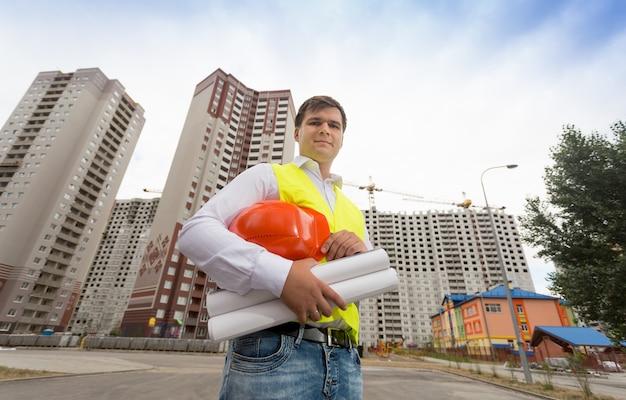 Portrait de jeune ingénieur en construction en gilet de sécurité holding hardhat