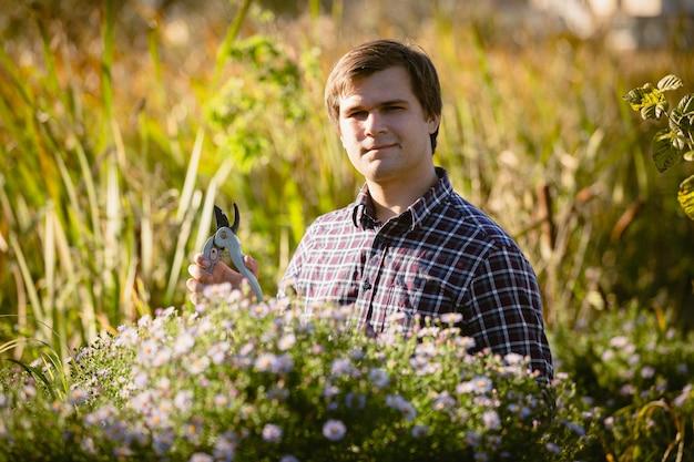 Portrait de jeune jardinier posant au parterre de fleurs