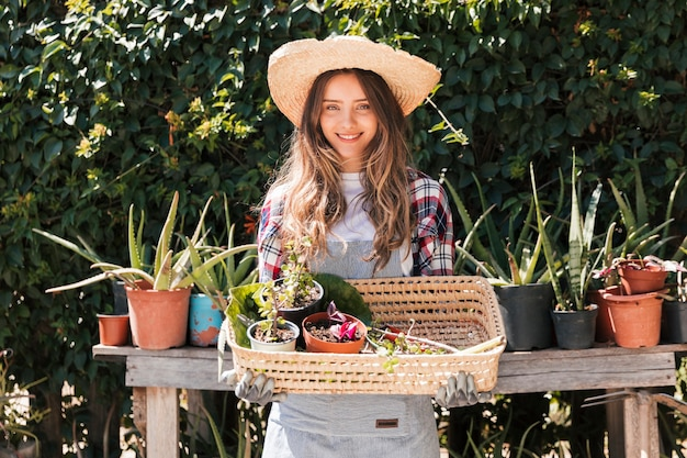 Portrait d'une jeune jardinière souriante tenant des plantes en pot dans le panier