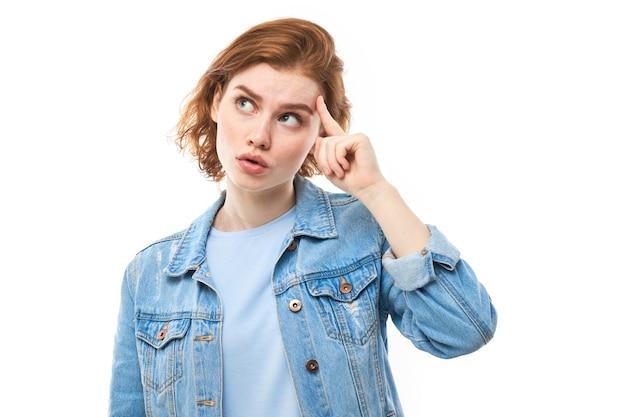 Portrait de jeune jolie belle étudiante rousse heureuse réfléchie pensant en regardant copyspace, isolé sur fond blanc. femme en jean bleu