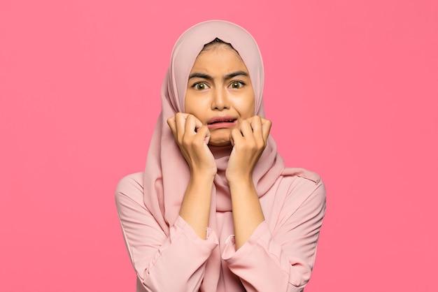 Portrait de jeune jolie femme asiatique panique et peur sur fond rose