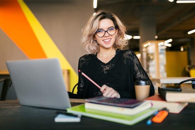 Portrait de jeune jolie femme assise à table en chemise noire travaillant sur ordinateur portable au bureau de co-working