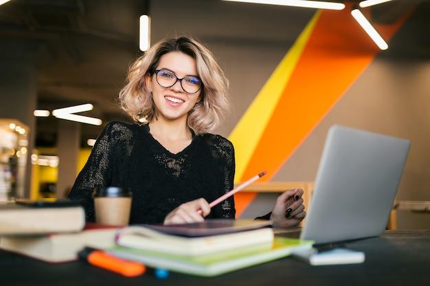 Portrait de jeune jolie femme assise à table en chemise noire travaillant sur ordinateur portable dans un bureau de co-working, portant des lunettes