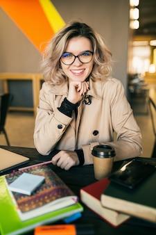 Portrait de jeune jolie femme assise à table en trench-coat travaillant sur ordinateur portable au bureau de travail, portant des lunettes, souriant, heureux, positif, lieu de travail