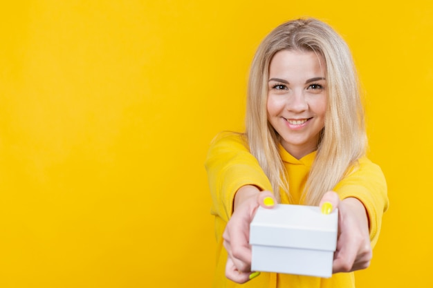 Portrait de jeune jolie femme blonde caucasienne heureuse en costume sportif jaune, donnez une boîte-cadeau blanche