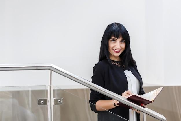 Portrait de jeune jolie femme brune heureuse vêtu d'un costume noir travaillant avec un ordinateur portable, debout dans le bureau, souriant, regardant la caméra.