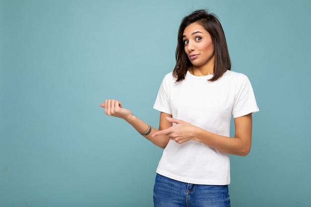 Portrait de jeune jolie femme brune séduisante avec des émotions sincères portant un t-shirt blanc décontracté pour maquette isolé sur fond bleu avec espace de copie et pointant vers un espace vide pour le texte.