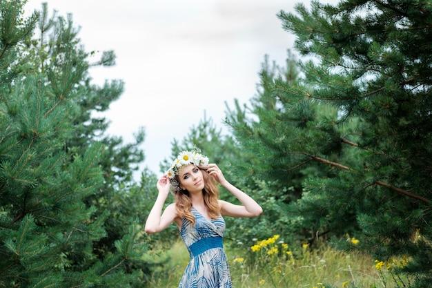 Portrait de jeune jolie femme avec un cercle de fleurs de camomille sur la tête, à l'extérieur, la coiffure