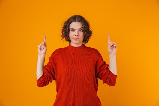Portrait d'une jeune jolie femme confuse posant isolé sur mur jaune pointant.