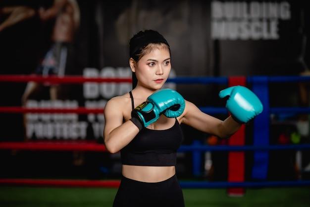 Portrait jeune jolie femme en gants de boxe pose debout sur toile dans une salle de fitness, classe de boxe d'entraînement fille saine,