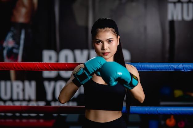 Portrait jeune jolie femme en gants de boxe pose debout sur toile dans une salle de fitness, cours de boxe d'entraînement pour fille en bonne santé, visage de mise au point sélective de dame,