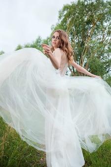 Portrait de jeune jolie femme (mariée) en robe de mariée blanche à l'extérieur, coiffure